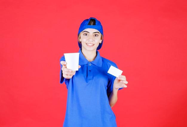음료 한 잔을 들고 그녀의 명함을 제시하는 파란색 유니폼 여성 서비스 요원.