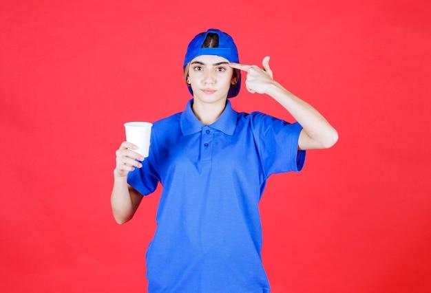 일회용 음료 한 잔을 들고 좋은 생각을 갖는 파란색 유니폼 여성 서비스 요원.