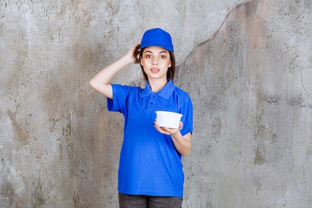 プラスチック製のボウルを持っている青い制服を着た女性のサービスエージェントは、混乱して思慮深く見えるか、良い考えを持っています。