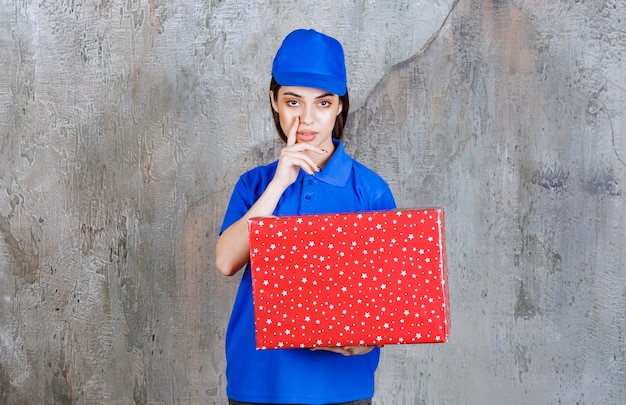 白い点が付いた赤いギフトボックスを持っている青い制服を着た女性サービスエージェントは、思慮深く、夢のように見えます。