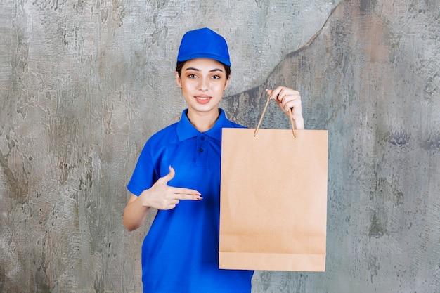 ショッピングバッグを保持している青い制服を着た女性サービスエージェント。