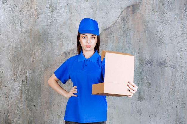 Женский агент службы в синей форме, держащей открытую картонную коробку.