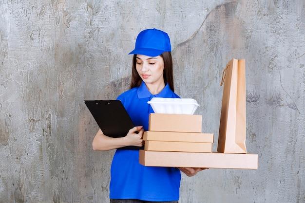 段ボール箱、ショッピングバックスとtaeawayボックスと黒い顧客フォルダーを保持している青い制服を着た女性サービスエージェント