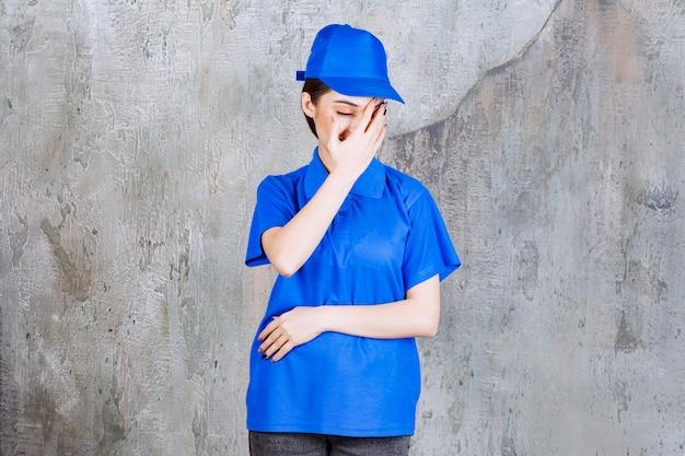 青い制服を着た女性サービスエージェントは疲れて眠そうに見えます。