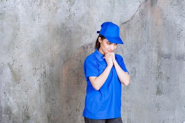 青い制服を着た女性サービスエージェントが胸に手を置き、混乱しているか思慮深く見えます。