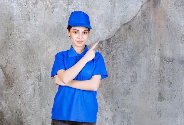 오른쪽을 보여주는 파란색 유니폼 여성 서비스 요원.