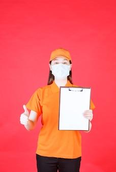 プロジェクトシートを示し、楽しみのサインを示すオレンジ色のドレスコードとマスクの女性サービスエージェント
