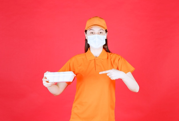 オレンジ色のドレスコードと持ち帰り用食品パッケージを保持しているマスクの女性サービスエージェント