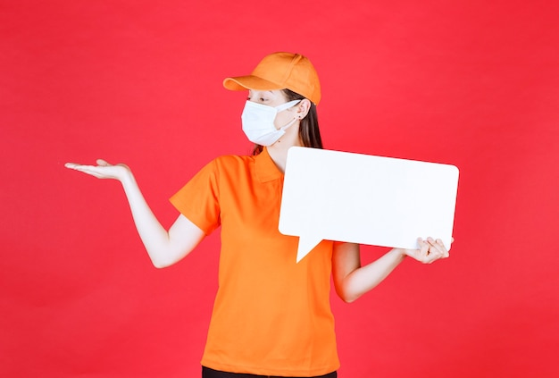 オレンジ色のドレスコードと白い長方形の情報ボードを保持し、周りの何かを指しているマスクの女性サービスエージェント