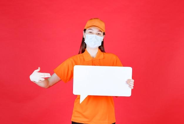 オレンジ色のドレスコードと白い長方形の情報ボードを保持しているマスクの女性サービスエージェント