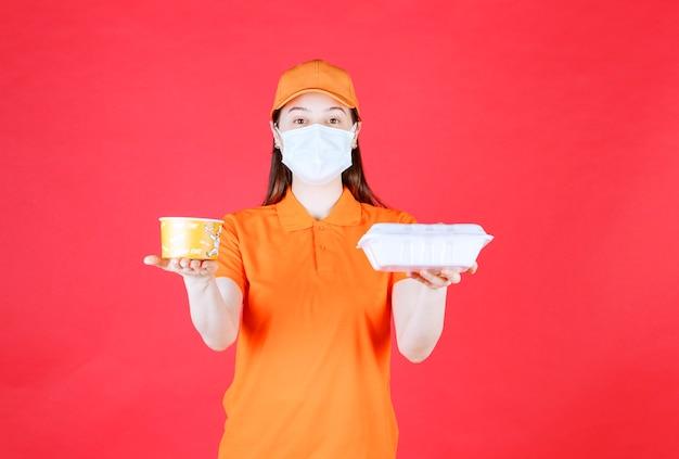 주황색 드레스코드와 테이크아웃 음식 패키지를 들고 있는 마스크를 쓴 여성 서비스 에이전트