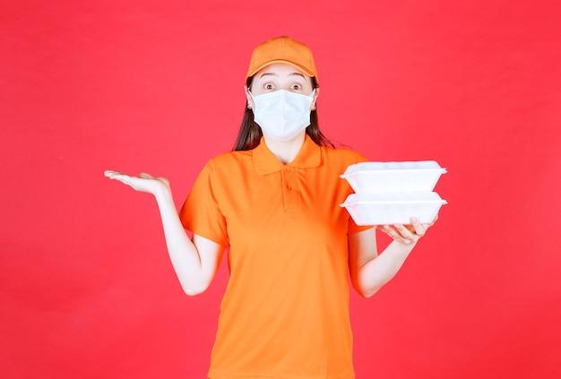주황색 드레스코드와 테이크아웃 음식 패키지 두 개를 들고 있는 마스크를 쓴 여성 서비스 요원