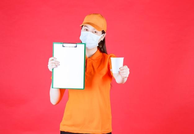 Женский сервисный агент в оранжевом дресс-коде и маске представляет одноразовую чашку нового бренда и показывает прайс-лист