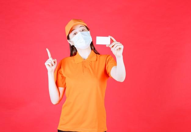 オレンジ色のドレスコードとマスクの女性サービスエージェントが名刺を提示し、他の誰かを指しています
