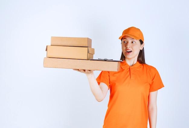 Женщина-агент службы в оранжевом дресс-коде доставляет несколько картонных коробок.