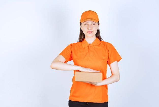 段ボール箱を保持しているオレンジ色のドレスコードの女性サービスエージェント