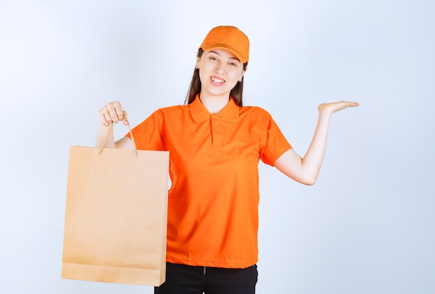 段ボールの買い物袋を保持しているオレンジ色のドレスコードの女性サービスエージェント