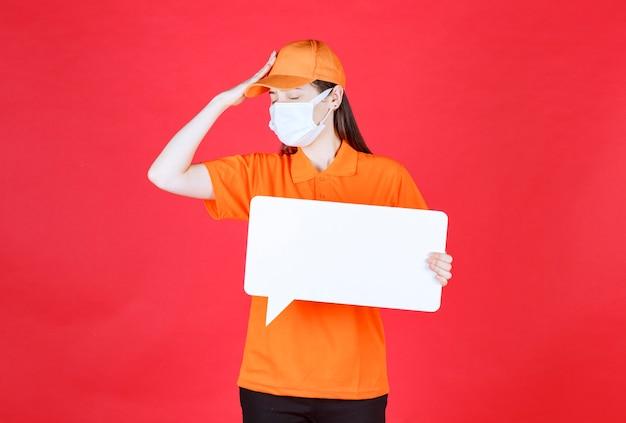 オレンジ色の制服と白い長方形の情報ボードを保持しているマスクの女性サービスエージェントは、疲れて眠そうに見えます。
