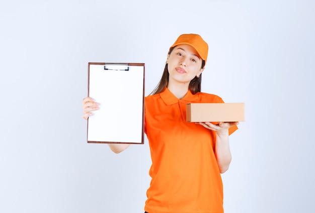 段ボール箱を保持し、署名のチェックリストを提示するオレンジ色の制服を着た女性サービスエージェント。