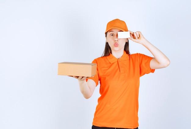 段ボール箱を持って名刺を提示するオレンジ色の制服を着た女性サービスエージェント。