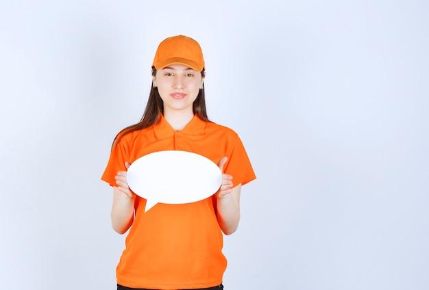 卵形の情報ボードを保持しているオレンジ色の制服を着た女性サービスエージェント。