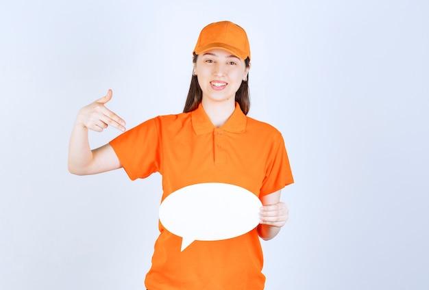 Агент женских услуг в форме оранжевого цвета, держащий информационное табло овале.