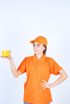 黄色のテイクアウトカップを保持しているオレンジ色の制服を着た女性サービスエージェント