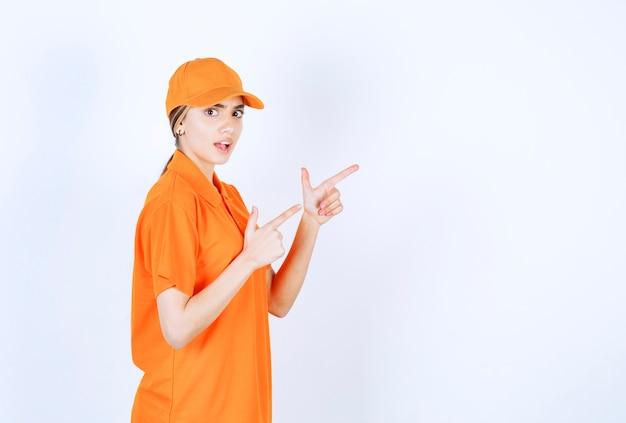 オレンジ色の制服を着た女性サービスエージェントが脇を指しています 無料写真