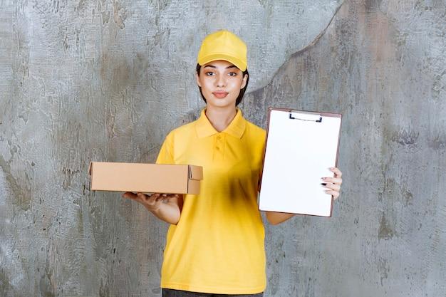 段ボール箱を持って署名を求める黄色い制服を着た女性サービスエージェント。