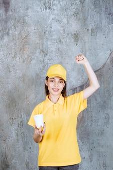 Агент женской службы в желтой форме держит пластиковый стаканчик и показывает знак рукой.