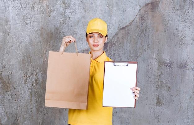 ショッピングバッグを持って署名を求める黄色い制服を着た女性サービスエージェント。