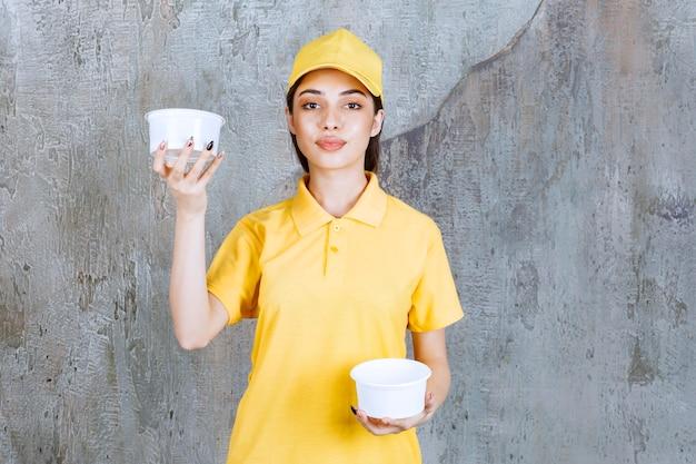 両手に2つのプラスチック製の持ち帰り用ボウルを保持している黄色の制服を着た女性サービスエージェント