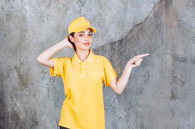 콘크리트 벽에 서서 오른쪽을 가리키는 노란색 유니폼을 입은 여성 서비스 요원.