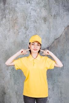 Агент женской службы в желтой форме стоит на бетонной стене и показывает себя.