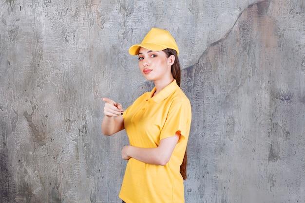 Агент женской службы в желтой форме стоит на бетонной стене и показывает человека впереди.