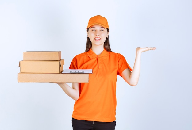 Agente di servizio femminile in codice di abbigliamento di colore arancione che consegna più scatole di cartone e indica da qualche parte