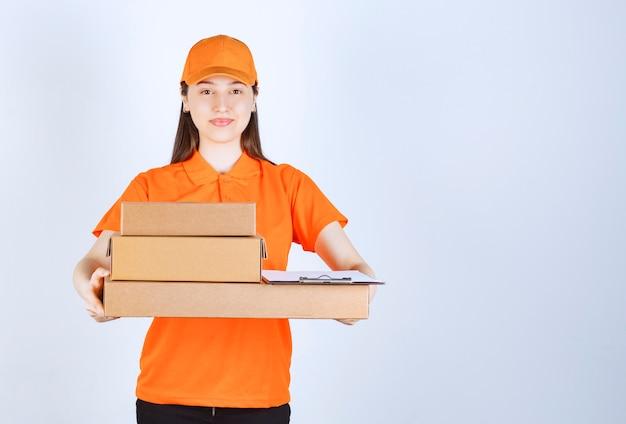 Agente di servizio femminile in dresscode di colore arancione che consegna più scatole di cartone