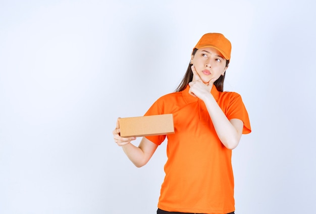 Female service agent in orange color dresscode holding a cardboard box, looks thoughtful and dreaming.