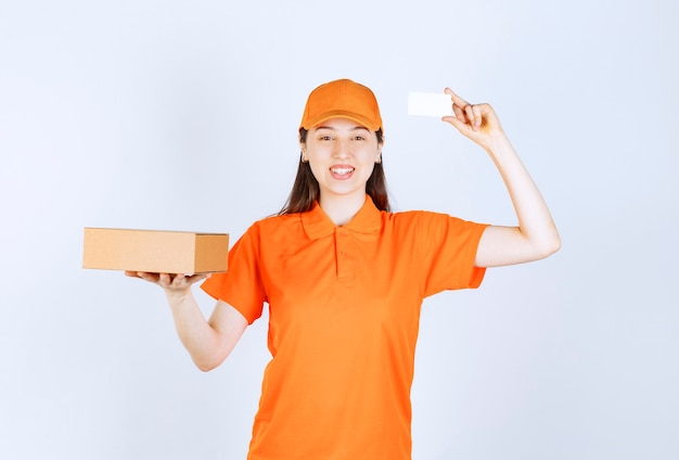 Female service agent in orange color dresscode holding a cardboard box and presenting her business card