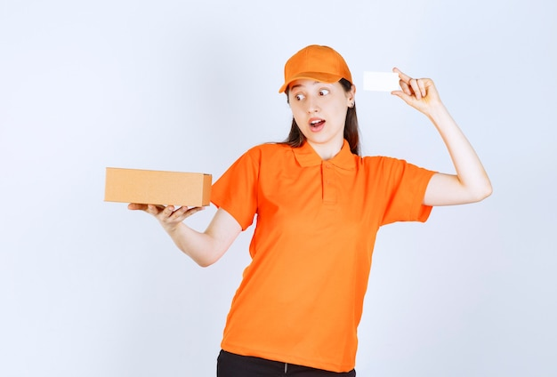 Female service agent in orange color dresscode holding a cardboard box and presenting her business card.
