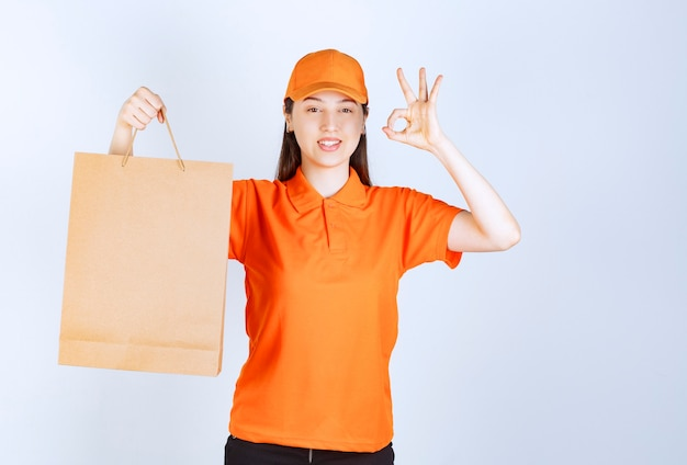 Female service agent in orange color dresscode holding a cardboard shopping bag and showing successful hand sign meaning quality assurance