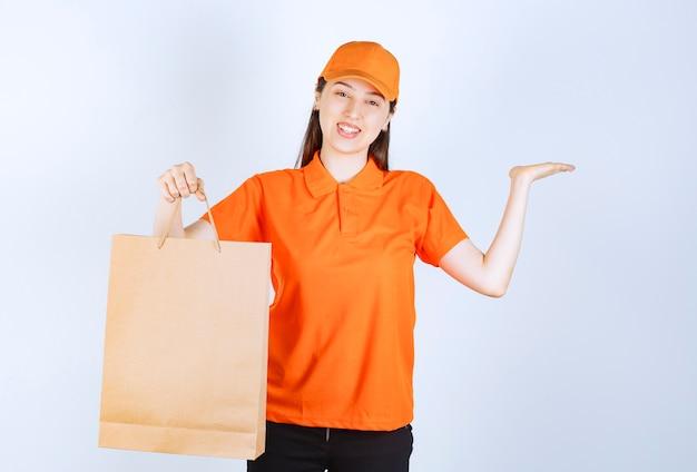 Female service agent in orange color dresscode holding a cardboard shopping bag