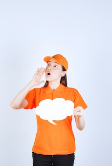 Female service agent in orange color dresscode holding a cloud shape info board and shouting or whispering