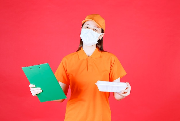Female service agent in orange color dresscode and mask holding a takeaway food package and checking the green folder