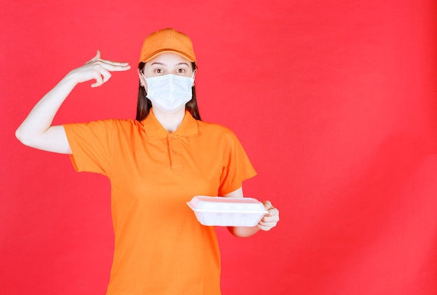Female service agent in orange color dresscode and mask holding a takeaway food package and looks thoughtful and dreaming