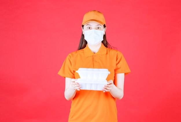 Agente di servizio femminile in codice di abbigliamento di colore arancione e maschera con due pacchetti di cibo da asporto