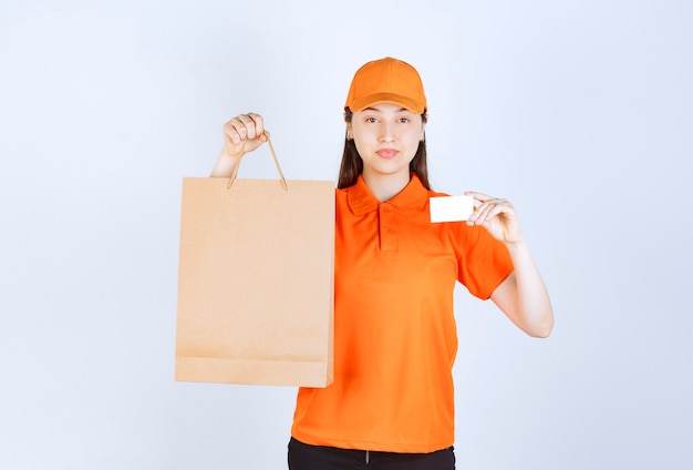 Female service agent in orange color uniform holding a cardboard shopping bag and presenting her business card.