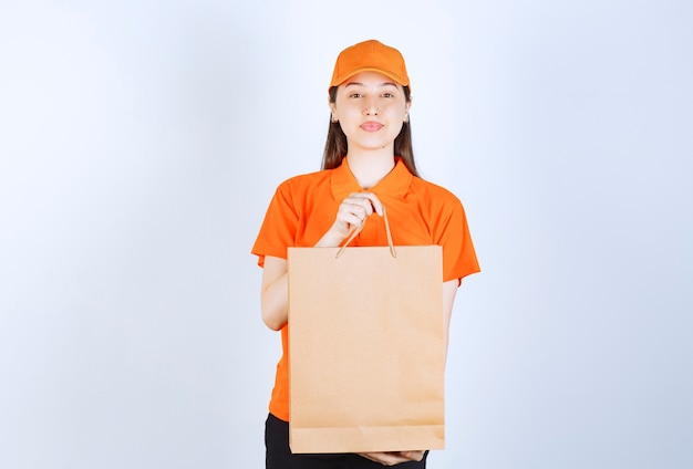 Female service agent in orange color uniform holding a cardboard shopping bag and presenting it to the customer.