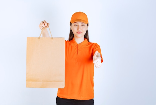 Female service agent in orange color uniform holding a cardboard shopping bag and showing successful hand sign meaning quality assurance.