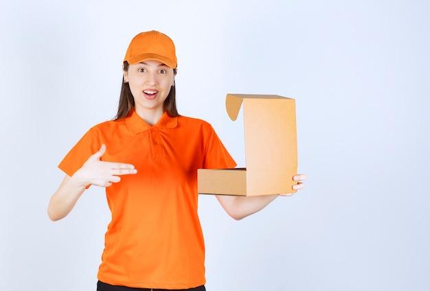Female service agent in orange color uniform holding an open cardboard box.